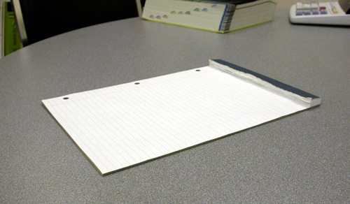 Photograph of a pad of paper with one sheet left.